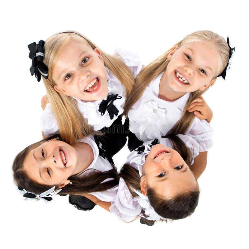 Grupp av att le skolflickor som isoleras på vit bakgrund royaltyfri fotografi