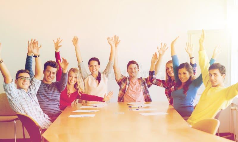 Grupp av att le studenter som i regeringsställning lyfter händer arkivfoto