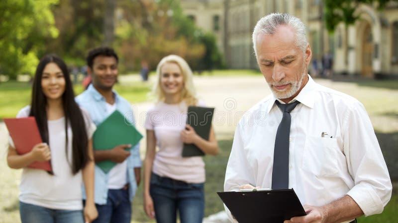 Grupp av att le studenter som står nära högskolan, upptagen manlig dekan som kontrollerar legitimationshandlingar arkivfoto