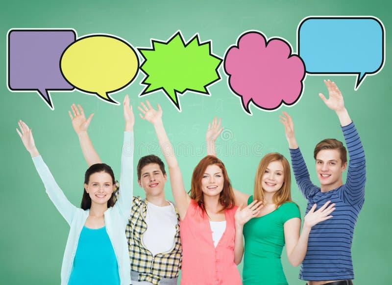Grupp av att le tonåringar med textbubblor royaltyfria bilder