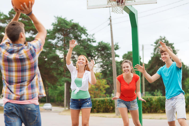 Grupp av att le tonåringar som spelar basket arkivbild