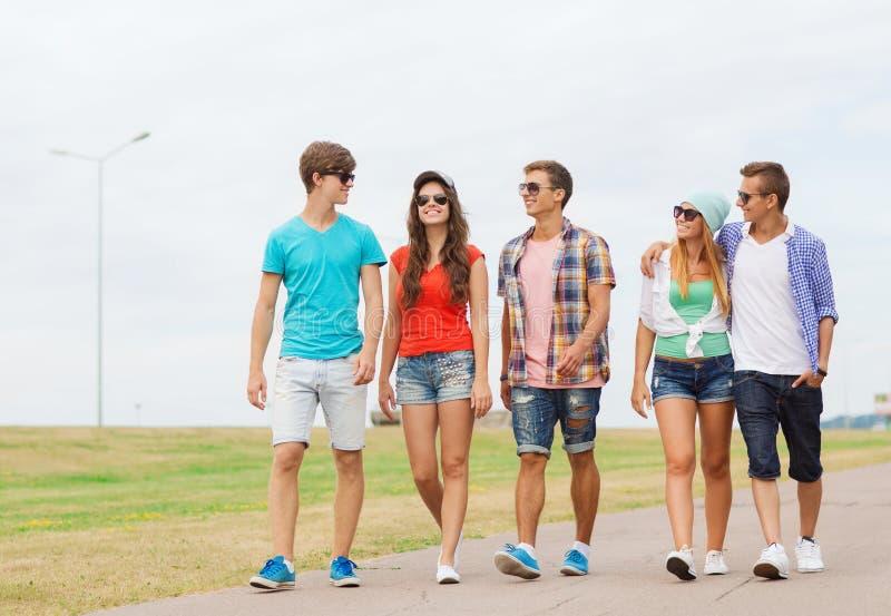 Grupp av att le tonåringar som utomhus går royaltyfri bild