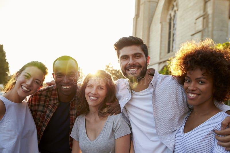 Grupp av att le unga vuxna vänner som omfamnar i gatan royaltyfri bild