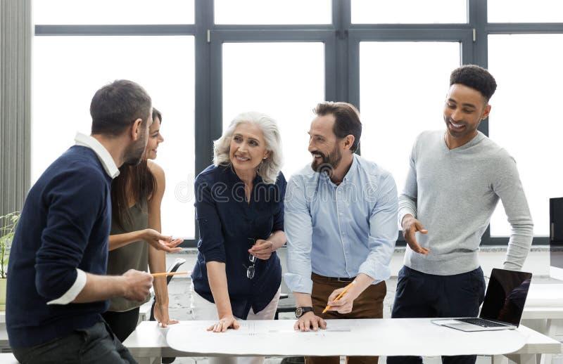 Grupp av att le upptaget diskutera för affärsfolk royaltyfri bild