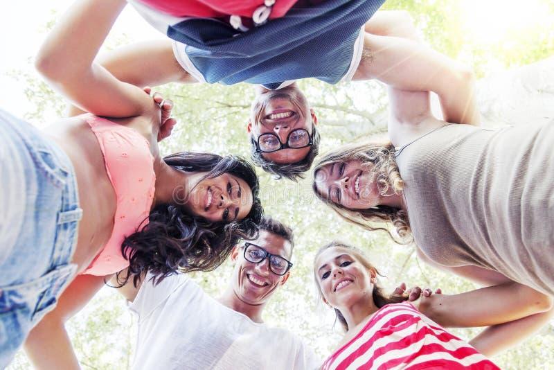 Grupp av att le vänner i cirkel royaltyfri foto