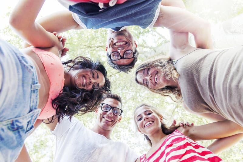 Grupp av att le vänner i cirkeln - nedersta sikt royaltyfria foton