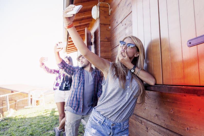 Grupp av att le vänner i gåsmarschen som tar rolig selfie fotografering för bildbyråer