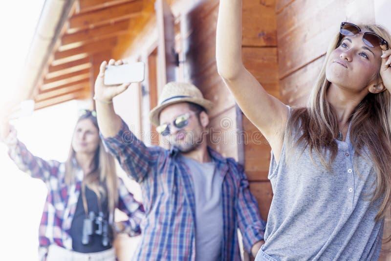 Grupp av att le vänner i gåsmarschen som tar rolig selfie arkivfoton
