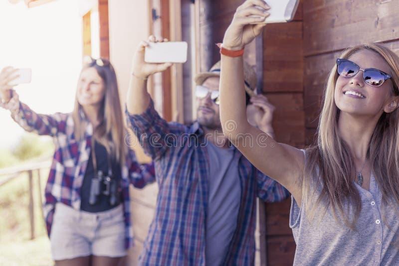 Grupp av att le vänner i gåsmarschen som tar rolig selfie royaltyfri foto