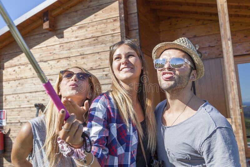 Grupp av att le vänner i gåsmarschen som tar rolig selfie royaltyfri bild