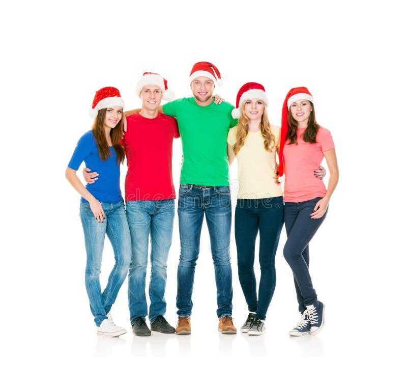 Grupp av att le vänner i julhattar arkivfoto