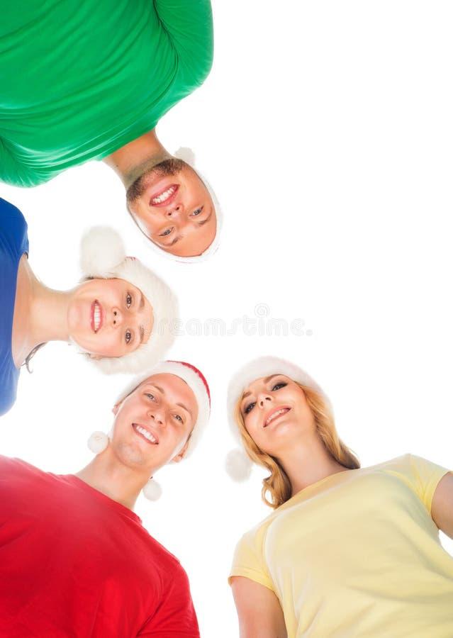 Grupp av att le vänner i julhattar som tillsammans omfamnar arkivfoto