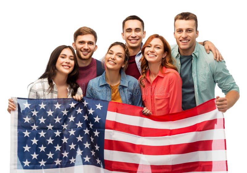 Grupp av att le vänner med amerikanska flaggan arkivfoton