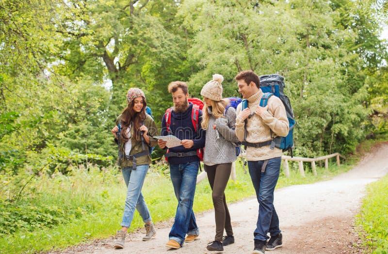 Grupp av att le vänner med att fotvandra för ryggsäckar royaltyfri bild