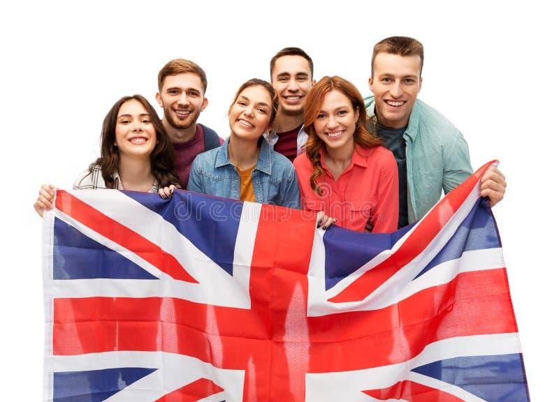 Grupp av att le vänner med den brittiska flaggan royaltyfria foton