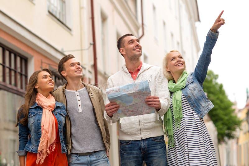 Grupp av att le vänner med den undersökande staden för översikt royaltyfria bilder