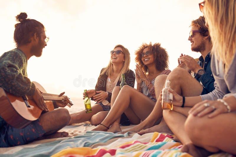 Grupp av att le vänner som har gyckel på stranden royaltyfria foton