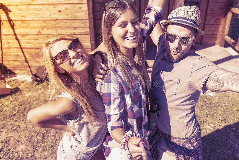 Grupp av att le vänner som tar rolig selfie med den smarta telefonen arkivfoto