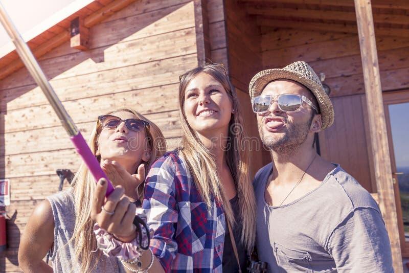 Grupp av att le vänner som tar rolig selfie med den smarta telefonen arkivbild