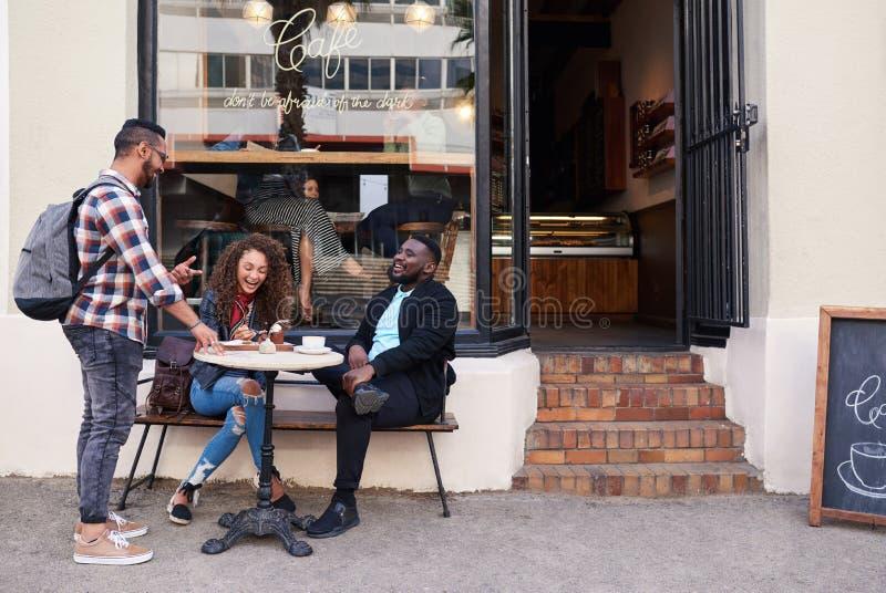 Grupp av att le vänner som tillsammans talar på ett trottoarkafé fotografering för bildbyråer