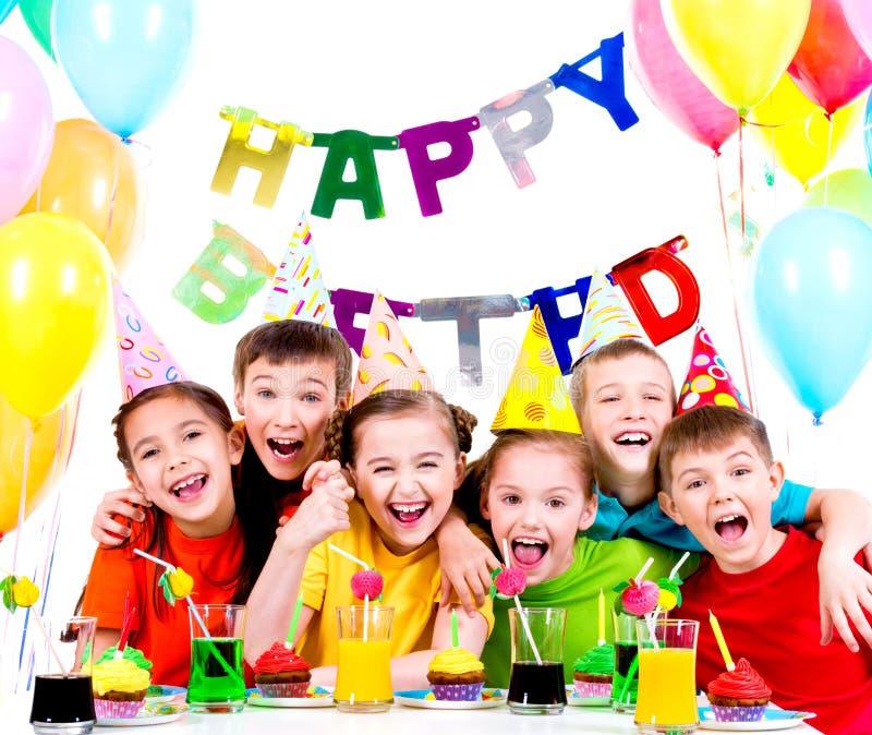 Grupp av att skratta ungar som har gyckel på födelsedagpartiet arkivbilder