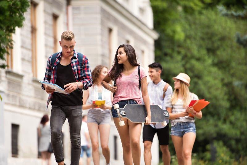 Grupp av attraktiva tonårs- studenter som går till universitetet royaltyfria foton