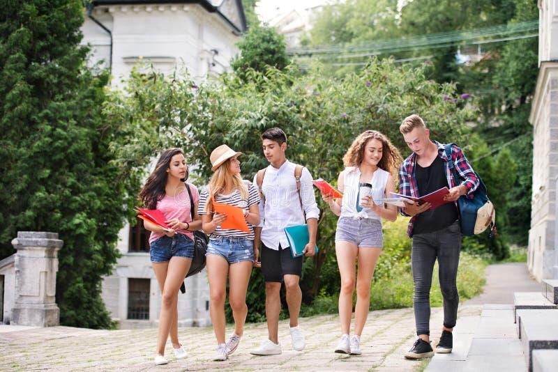 Grupp av attraktiva tonårs- studenter som går till universitetet arkivbild