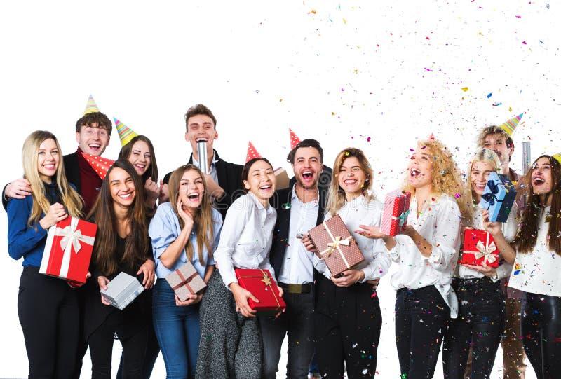 Grupp av attraktiva unga vänner som står över vit bakgrund arkivbilder
