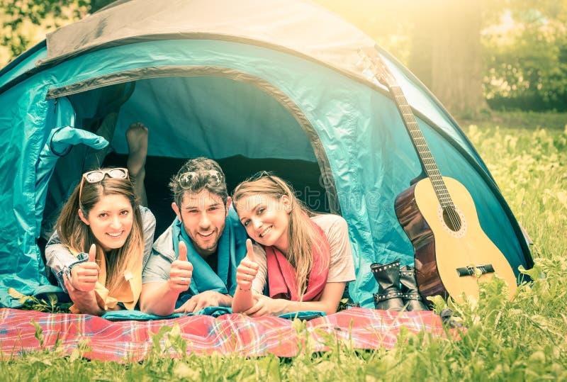 Grupp av bästa vän med tummar upp i campa tält royaltyfri fotografi