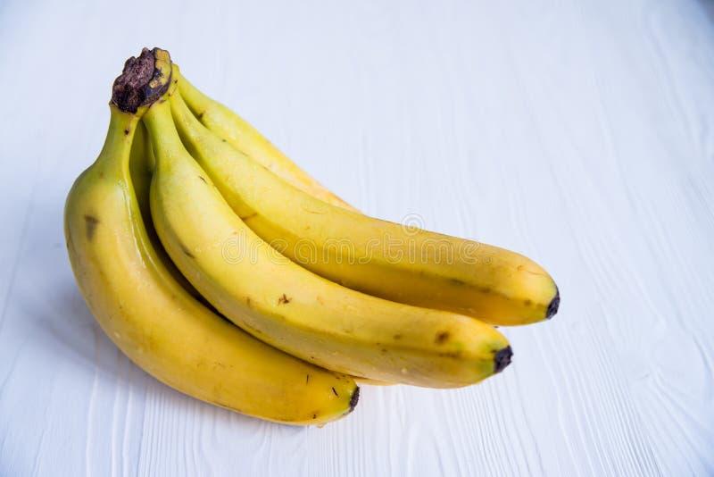 Grupp av bananer på det vita träyttersidaslutet royaltyfria bilder