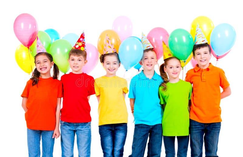 Grupp av barn i kulöra t-skjortor och partihattar fotografering för bildbyråer