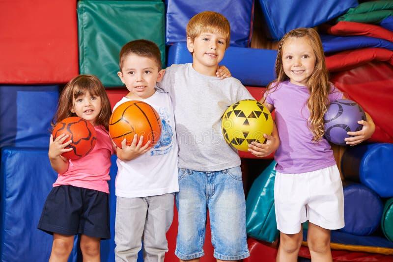 Grupp av barn med bollar i idrottshall royaltyfria bilder