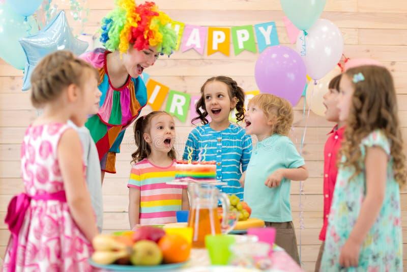 Grupp av barn med clownen som blåser stearinljus på kakan på födelsedagpartiet arkivbilder