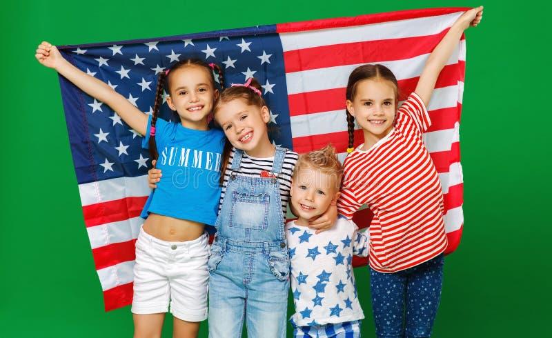 Grupp av barn med flaggan av Amerikas f?renta stater USA p? gr?n bakgrund royaltyfri fotografi