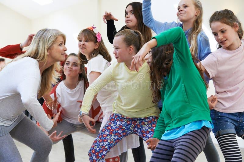 Grupp av barn med läraren Enjoying Drama Class tillsammans arkivbild