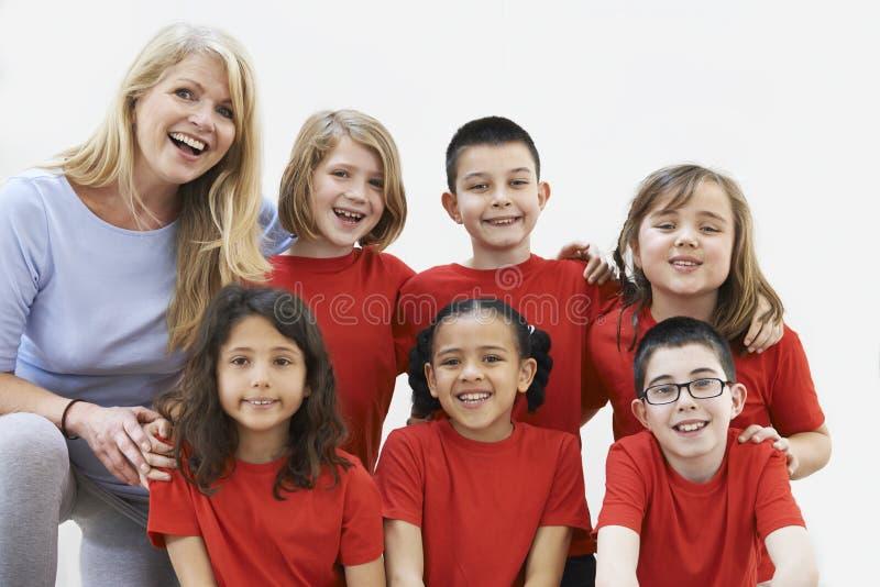 Grupp av barn med läraren Enjoying Drama Workshop tillsammans royaltyfria bilder