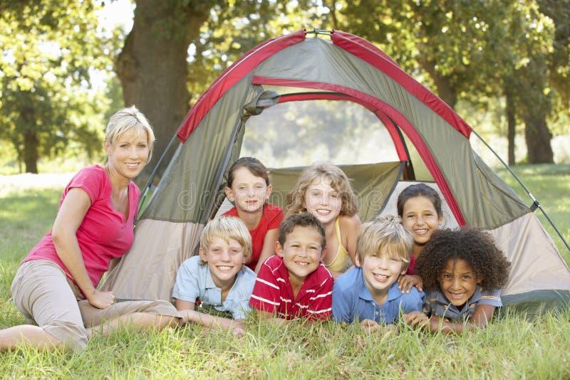 Grupp av barn med modern som har gyckel i tält i bygd royaltyfri fotografi