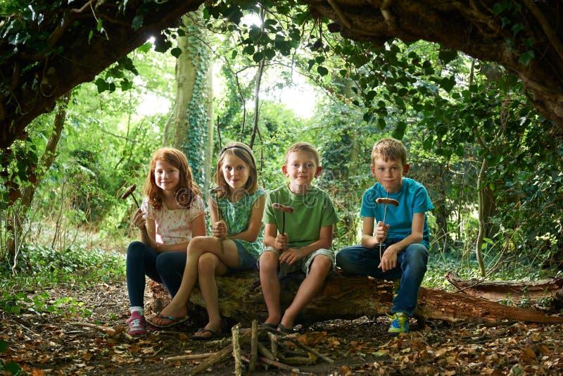 Grupp av barn som äter korvar i skogsmarkläger arkivbilder