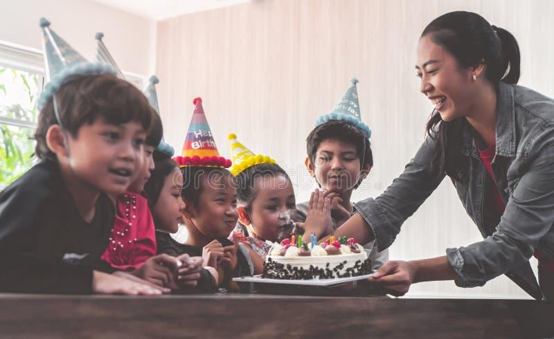 Grupp av barn som blåser födelsedagkakan i födelsedagpartiet som sjunger lycklig födelsedag arkivfoton