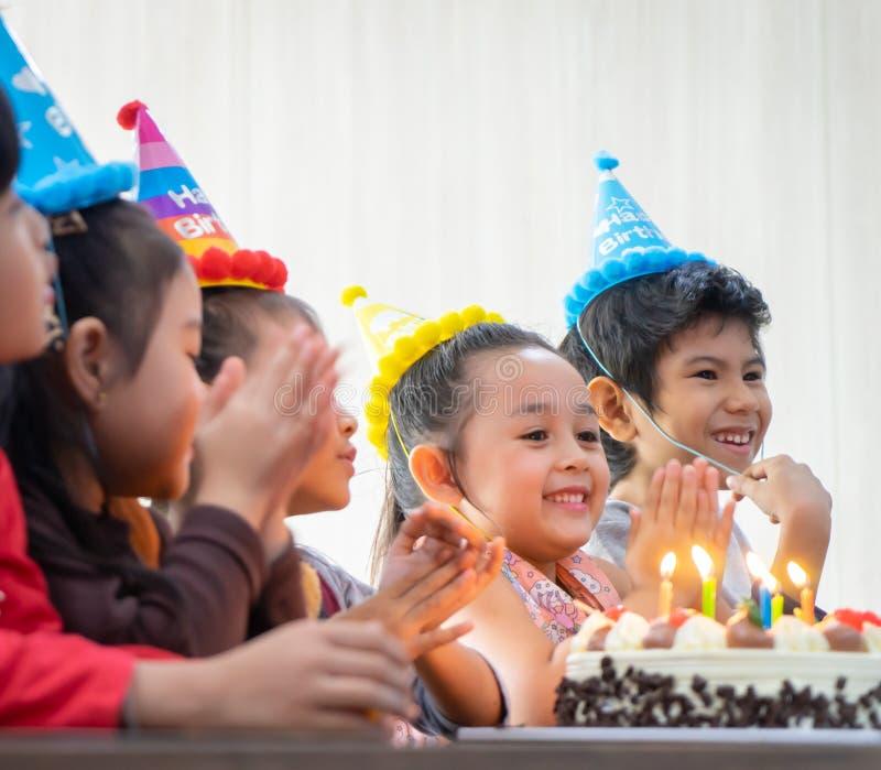 Grupp av barn som blåser födelsedagkakan i födelsedagpartiet som sjunger lycklig födelsedag arkivfoto