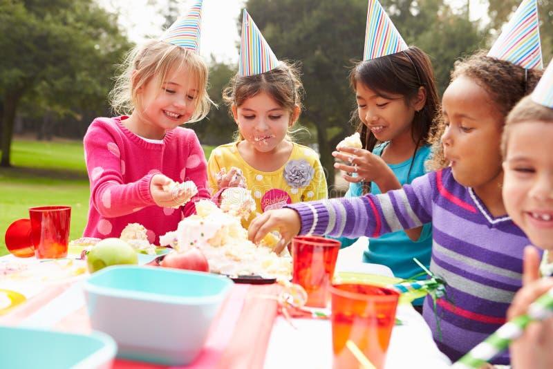 Grupp av barn som har det utomhus- födelsedagpartiet arkivfoton