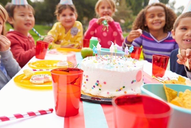 Grupp av barn som har det utomhus- födelsedagpartiet royaltyfria bilder