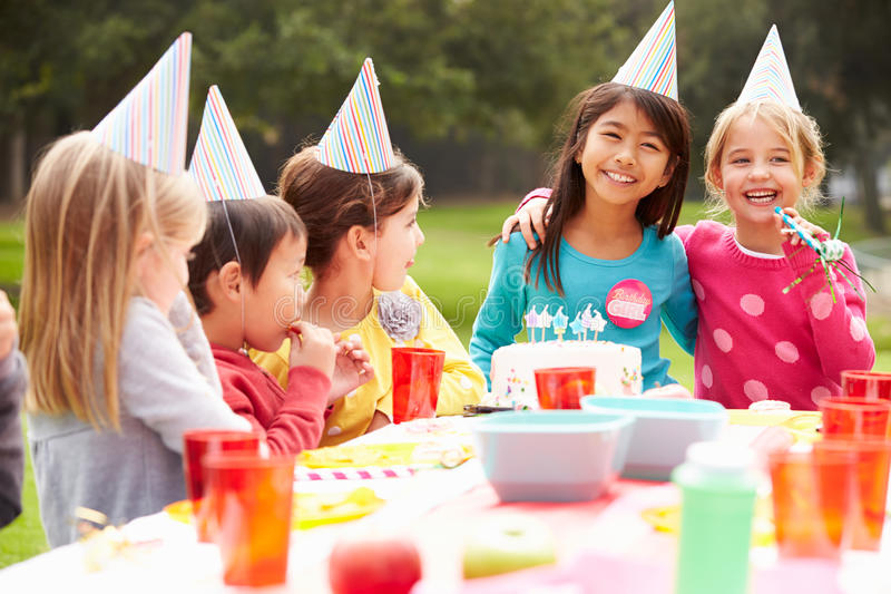Grupp av barn som har det utomhus- födelsedagpartiet arkivbild