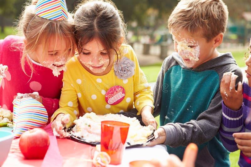 Grupp av barn som har det utomhus- födelsedagpartiet royaltyfri fotografi