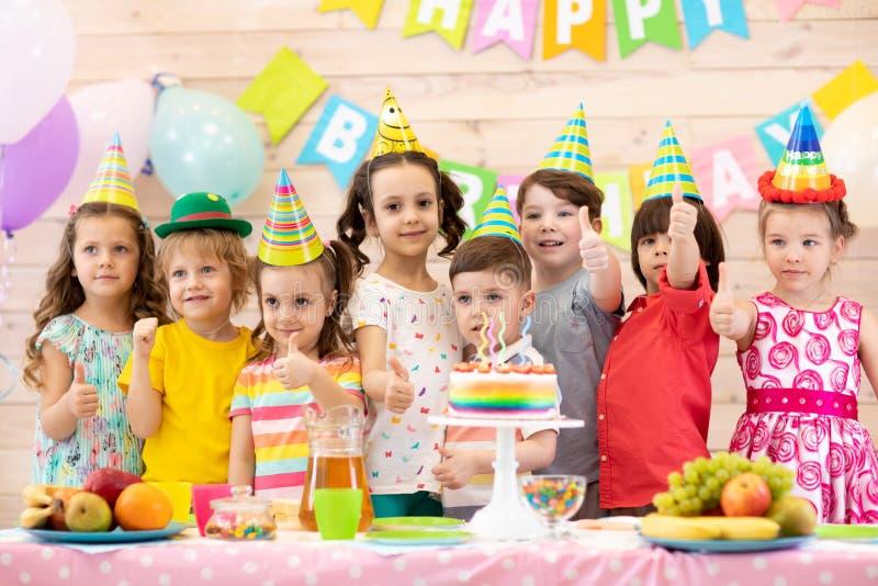 Grupp av barn som har gyckel som firar födelsedagpartiet Ungar som visar tummar upp tecken arkivfoton