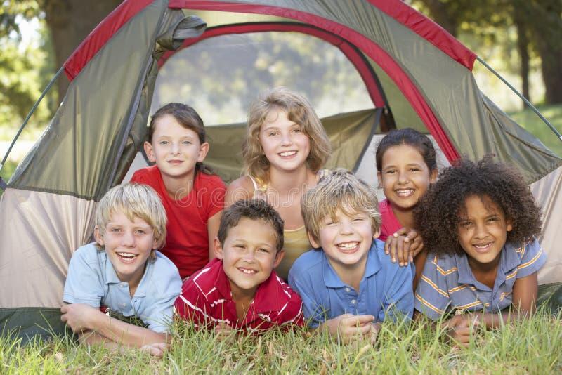 Grupp av barn som har gyckel i tält i bygd arkivbilder