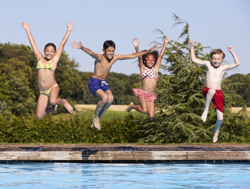 Grupp av barn som hoppar in i utomhus- simbassäng royaltyfri foto