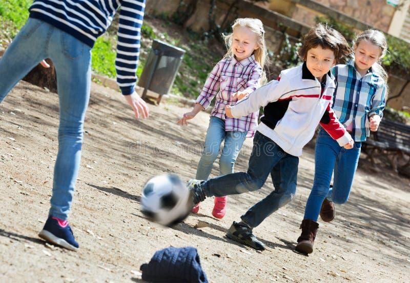 Grupp av barn som jagar bollen royaltyfri fotografi