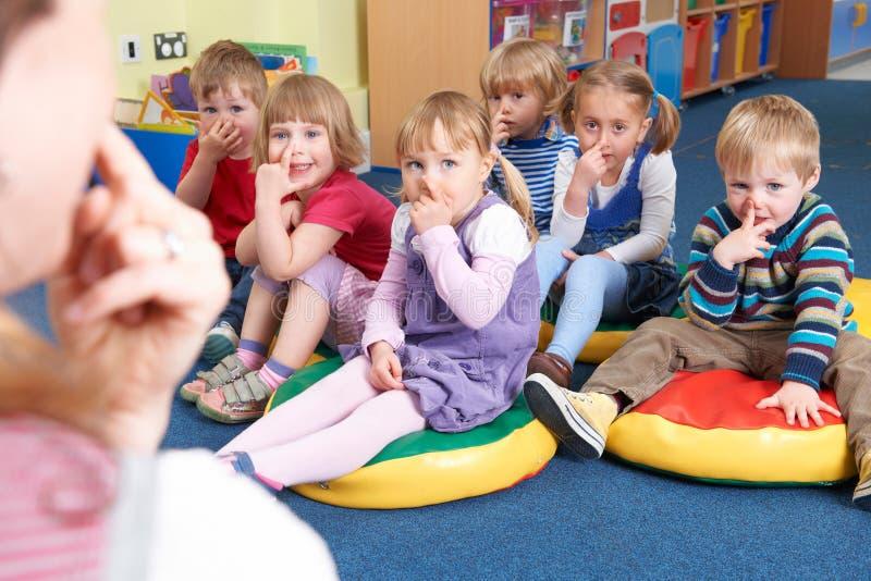 Grupp av barn som kopierar lärareIn Montessori /Pre-School grupp royaltyfri foto