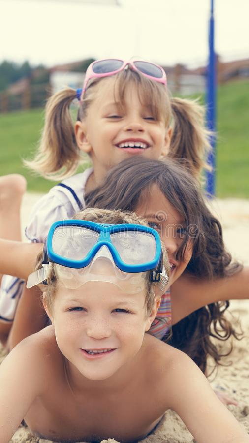 Grupp av barn som ligger på stranden, i sommar och att le royaltyfri fotografi